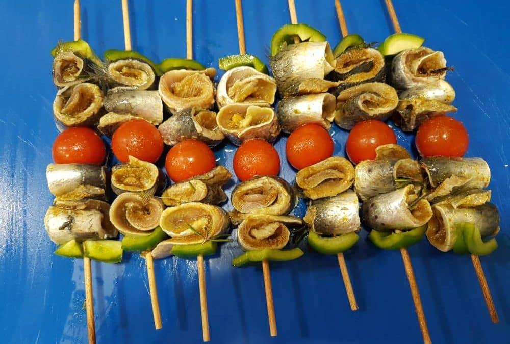 Brochettes de filets de sardine roulés marinés au citron et aux épices marocaines avec des poivrons verts et des tomates sur un plan de travail bleu