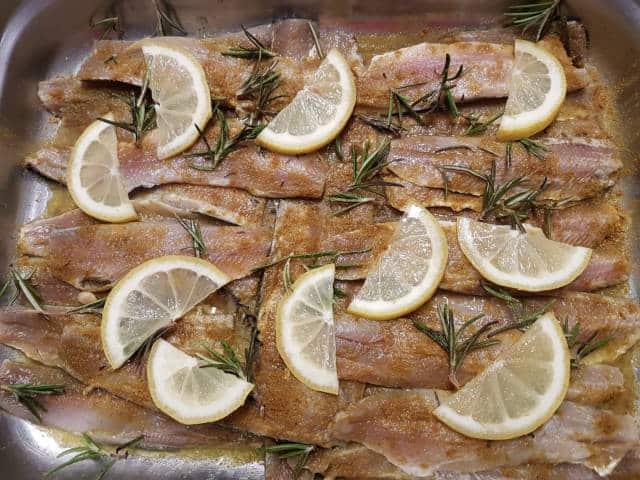 Filets de sardines dans un plat avec du citron et du romarin (marinade))