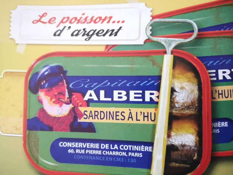 """Photos des boîtes de sardines produites dans la conserverie """"Le Poisson d'argent"""" au port de la Cotinière au siècle dernier."""